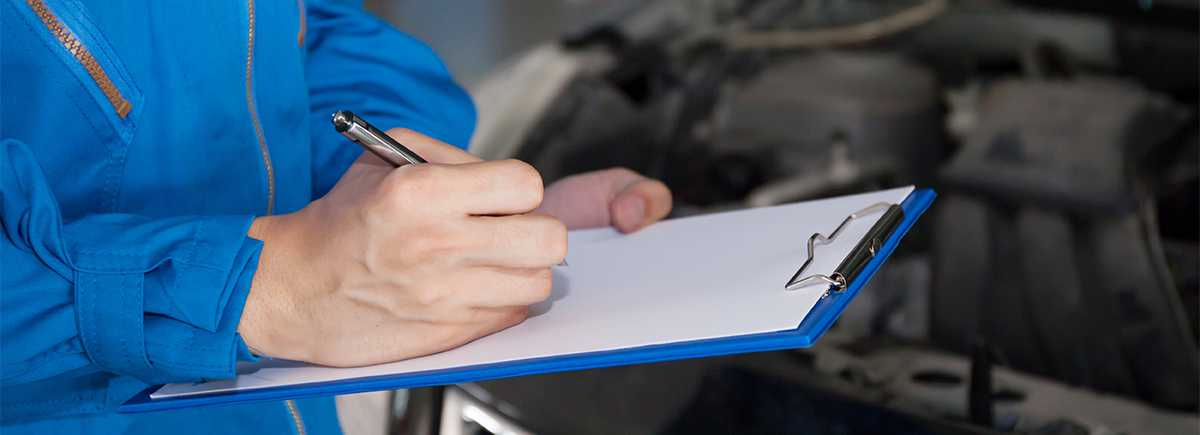 Technician completing a checklist for an MOT Liverpool's Mount Garage